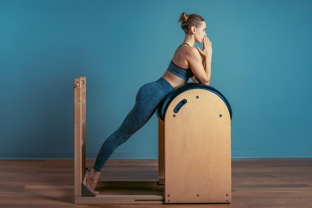 Młoda dziewczyna robi ćwiczenia pilates na łóżku reformatora. piękny, szczupły trener fitness na szarym tle reformera, niski klucz, światło sztuki. koncepcja fitness.