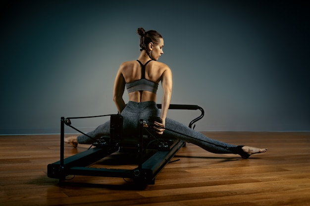 Młoda dziewczyna robi ćwiczenia pilates na łóżku reformatora