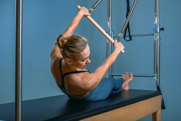 Młoda dziewczyna robi ćwiczenia pilates z łóżkiem reformatora. piękny, smukły trener fitness na reformatorskiej szarej ścianie, niski klucz, światło sztuki. koncepcja fitness