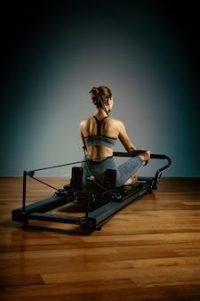 Młoda dziewczyna robi ćwiczenia pilates z łóżkiem reformatora. piękny, smukły trener fitness na reformerze