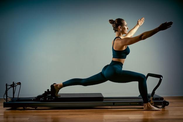 Młoda dziewczyna robi ćwiczenia pilates z łóżkiem reformatora. piękny szczupły trener fitness na szarym tle reformatora, niski klucz, światło sztuki. koncepcja fitness