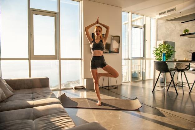 Młoda dziewczyna robi ćwiczenia siłowni podczas wschodu słońca. jest w domu z powodu kwarantanny koronawirusa codiv-19