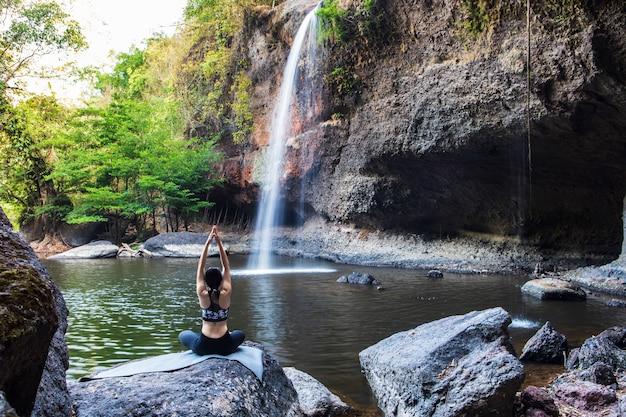 Młoda dziewczyna robi joga blisko siklawy