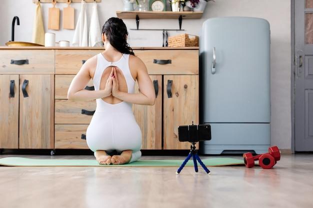Młoda dziewczyna robi joga sprawności fizycznej ćwiczeniu w domu