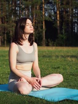 Młoda dziewczyna robi jogę w lesie, na zewnątrz w słoneczny letni dzień. dziewczyna stoi w stojaku, wykonuje asanę w parku. zdrowy styl życia, koncepcja medytacji. uroda i zdrowie kobiet.