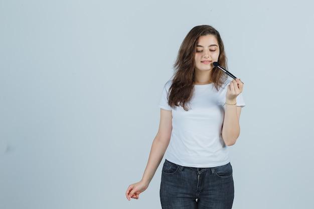 Młoda dziewczyna robi makijaż z pędzelkiem w t-shirt, dżinsy i wygląda uroczo, widok z przodu.