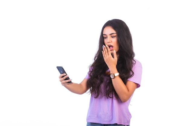 Młoda dziewczyna robi selfie lub prowadzi rozmowę wideo i zostaje zaskoczona