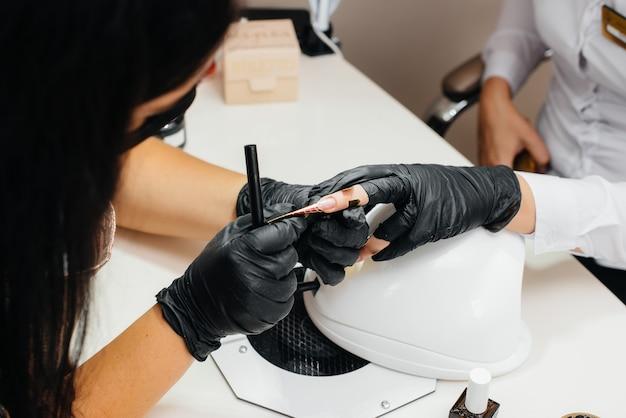 Młoda dziewczyna robi sobie manicure z bliska na dłoniach w salonie kosmetycznym