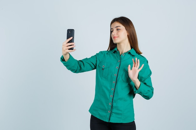 Młoda dziewczyna robi wideokonferencję, macha ręką, żeby się przywitać w zielonej bluzce, czarnych spodniach i wyglądającej wesoło, widok z przodu.