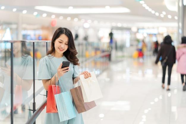 Młoda dziewczyna robi zakupy i korzysta z telefonu w centrum handlowym