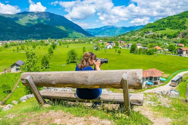 Młoda dziewczyna robi zdjęcia na drewnianej ławce w pobliżu źródeł ali paszy.