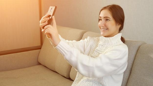 Młoda dziewczyna robi zdjęcie lub robi selfie w swojej sypialni, światło słoneczne