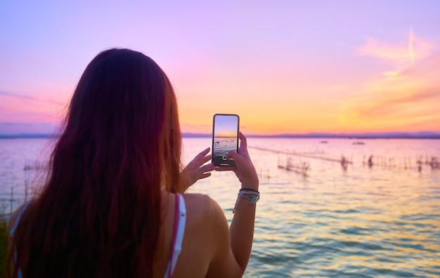 Młoda dziewczyna robi zdjęcie telefonem komórkowym w krajobrazie o zachodzie słońca. albufera z walencji. hiszpania