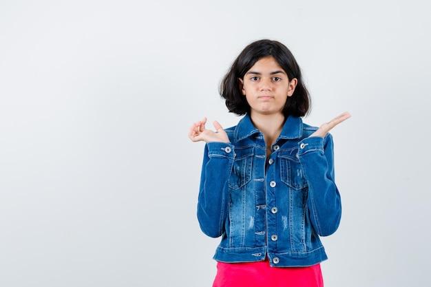 Młoda dziewczyna, rozciągając ręce w sposób przesłuchania w czerwonej koszulce i dżinsowej kurtce i patrząc poważnie, widok z przodu.