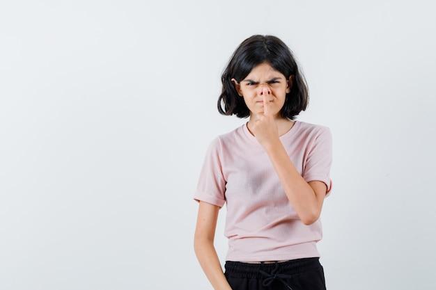Młoda dziewczyna rozciąganie nosa palcem wskazującym w różowej koszulce i czarnych spodniach i wyglądający zabawnie