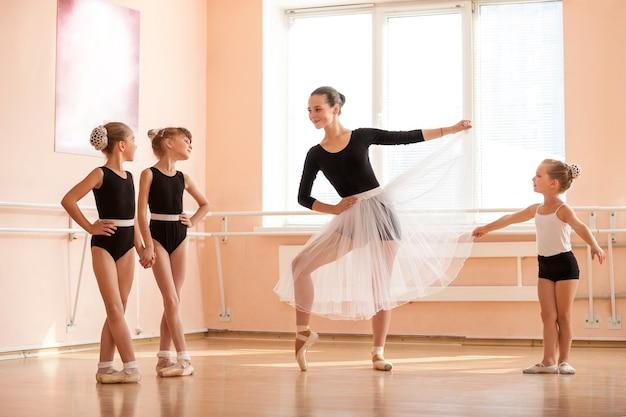Młoda dziewczyna rozgrzewa się i rozmawia z młodszymi kolegami z klasy na zajęciach tańca baletowego