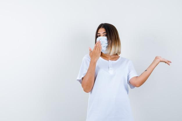 Młoda dziewczyna rozkłada dłoń na bok, pokazuje znak stop w białej koszulce i masce i wygląda na pewną siebie, widok z przodu.
