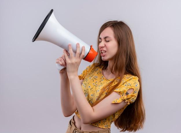Młoda dziewczyna rozmawia przez głośnik na na białym tle białej ścianie