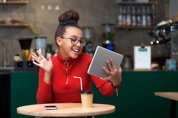 Młoda dziewczyna rozmawia przez łącze wideo, siedząc przy stoliku w kawiarni