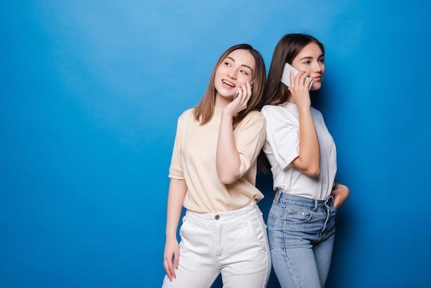 Młoda dziewczyna rozmawia przez telefon i inna dziewczyna używa telefonu na niebieskiej ścianie