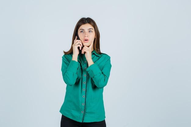 Młoda dziewczyna rozmawia przez telefon, kładzie palec wskazujący pod brodą w zielonej bluzce, czarnych spodniach i wygląda na zaskoczoną. przedni widok.