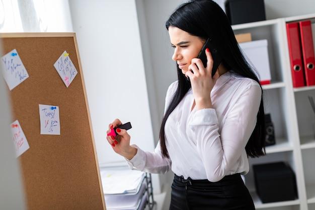 Młoda dziewczyna rozmawia przez telefon, trzymając w dłoni marker i stojąc przy tablicy z naklejkami.