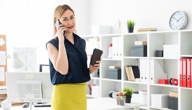 Młoda dziewczyna rozmawia przez telefon w biurze i trzyma szklankę kawy.