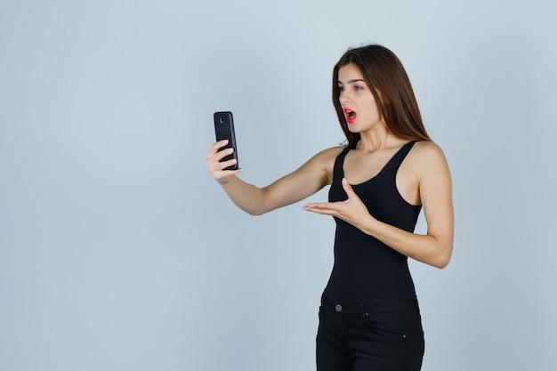Młoda dziewczyna rozmawia z kimś przez telefon, wyciągając rękę w kierunku telefonu w czarnej bluzce, spodniach i patrząc skupioną. przedni widok.