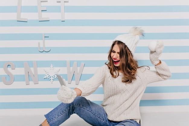 Młoda dziewczyna rozmawiająca selfie w dobrym nastroju śmieje się, radując się nadejściem zimy. pełnometrażowy portret kobiety z śnieżką w dłoniach