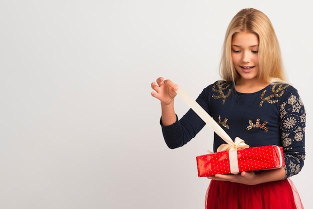 Młoda dziewczyna rozpakowywania prezent na boże narodzenie