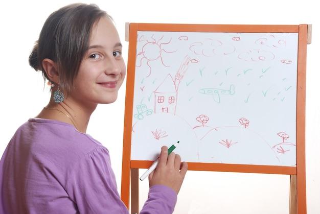 Młoda dziewczyna rysująca na białej tablicy