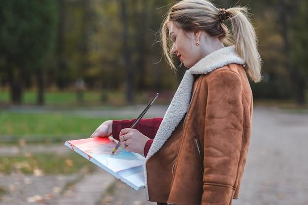 Młoda dziewczyna rysuje zdjęcie w parku