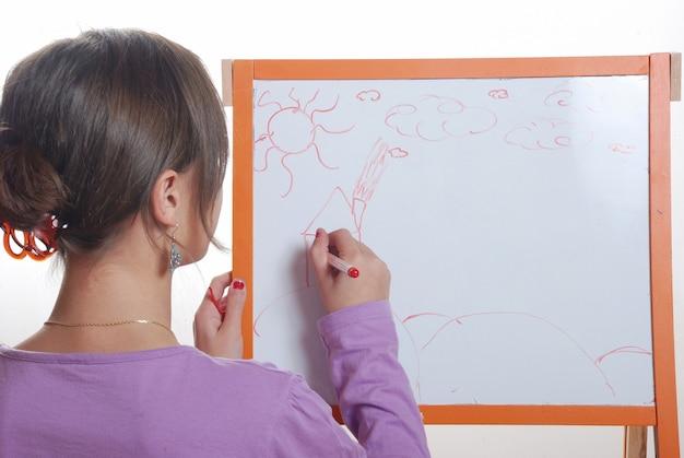 Młoda dziewczyna rysunek na białej desce
