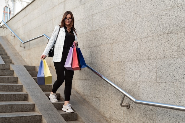 Młoda dziewczyna schodzi po schodach z kolorowych toreb na zakupy.