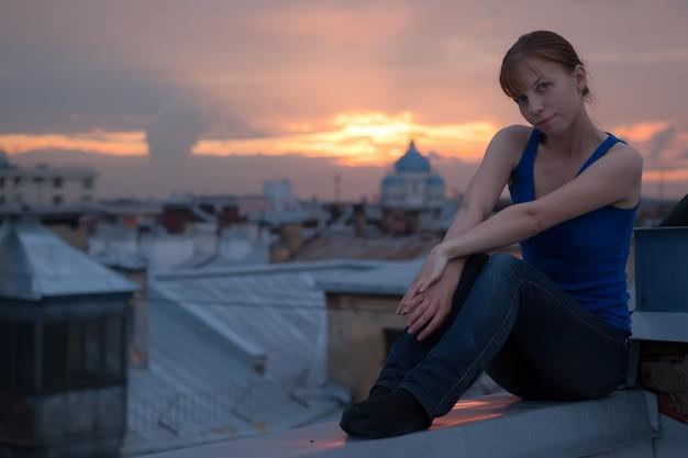 Młoda dziewczyna siedząca na dachu w centrum sankt-petersburga przed zachodem słońca