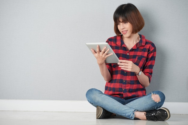 Młoda dziewczyna siedząca w pozycji lotosu przegląda sieć na swoim cyfrowym tablecie pc