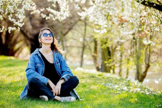 Młoda dziewczyna siedzi blisko kwiatonośnego drzewa w drelichowej kurtce i okularach przeciwsłonecznych