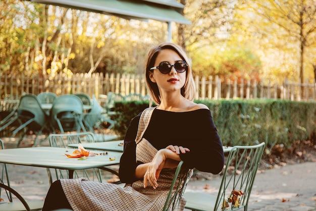 Młoda dziewczyna siedzi krzesła w kawiarni w okularach przeciwsłonecznych