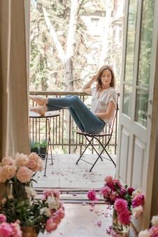 Młoda dziewczyna siedzi na balkonie