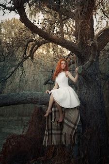 Młoda dziewczyna siedzi na drzewie w lesie