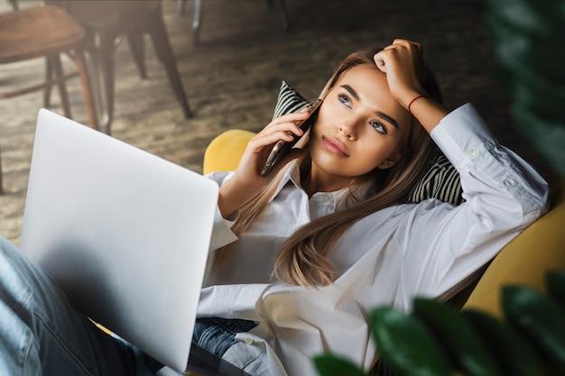 Młoda dziewczyna siedzi na kanapie z laptopem na kolanach, nawiązując rozmowę telefoniczną.