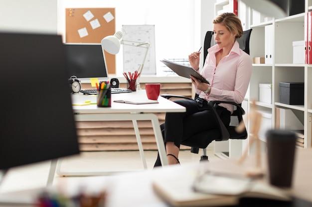 Młoda dziewczyna siedzi na krześle w biurze i trzyma w rękach dokumenty oraz ołówek.