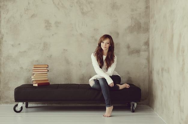 Młoda dziewczyna siedzi na ławce w pokoju