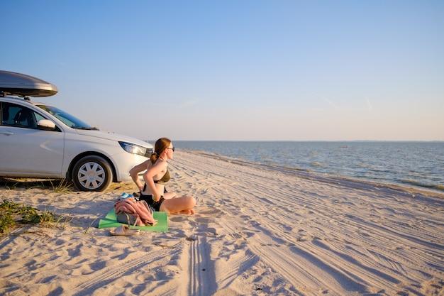 Młoda dziewczyna siedzi na plaży swoim samochodem