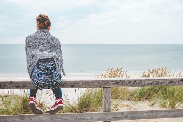 Młoda dziewczyna siedzi na plaży