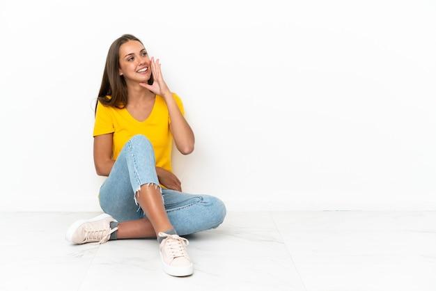 Młoda dziewczyna siedzi na podłodze krzycząc z szeroko otwartymi ustami na boki