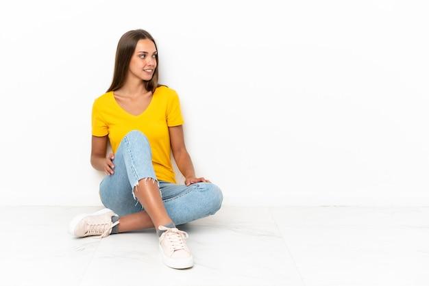 Młoda dziewczyna siedzi na podłodze patrząc z boku