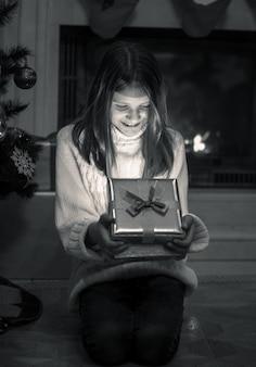 Młoda dziewczyna siedzi na podłodze przy kominku i otwiera świąteczne pudełko na prezent