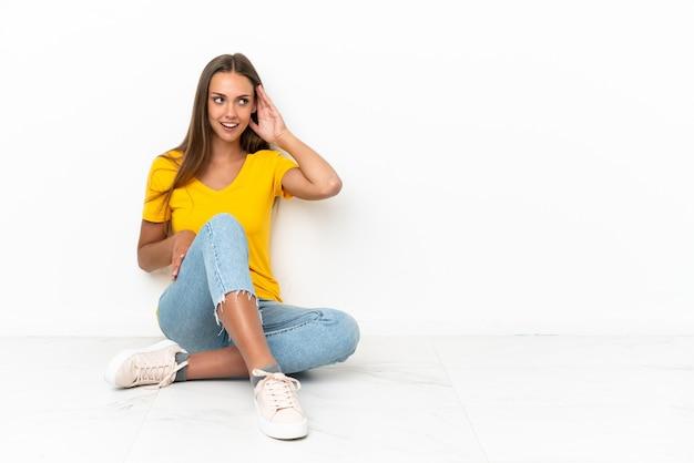 Młoda dziewczyna siedzi na podłodze, słuchając czegoś, kładąc rękę na uchu