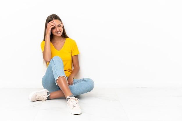 Młoda dziewczyna siedzi na podłodze śmiejąc się